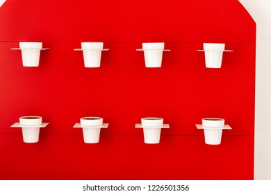 Eight white vases on the background of a red wall.