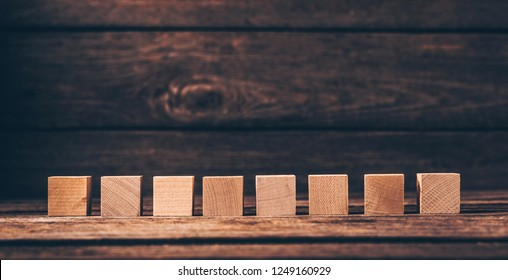 Eight Wooden Cubes on Wood Background with Copyspace