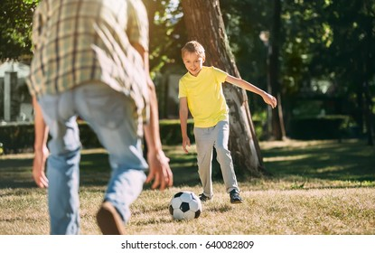 Eight year old boy playing football in a park with dad