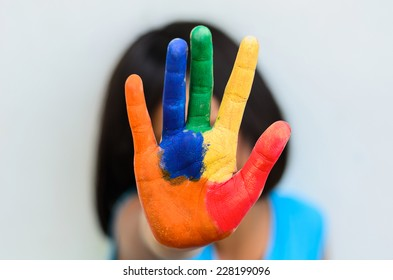 Eight year old girl with hand painted in colorful paints ready f