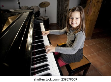 Eight year old girl is happy playing the piano