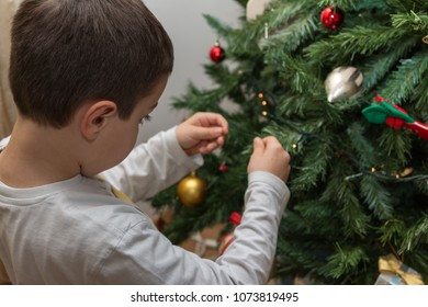 Eight Years Boy Hanging Balls and Decorations on Christmas Tree.