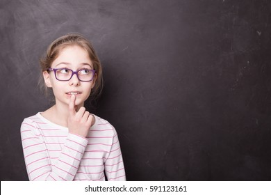 Eight years old, caucasian, blond child girl (kid, pupil) thinking or imaging something at the school blackboard (chalkboard). Background with free text (copy) space. Education and childhood concept.