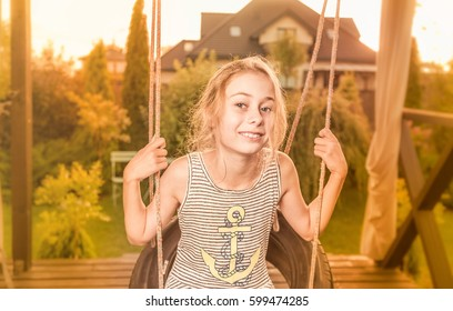 Eight years old, caucasian, happy smiling blond child girl (kid) outdoor in the garden on the swing. Summer vacation and careless childhood concept in sepia tone.