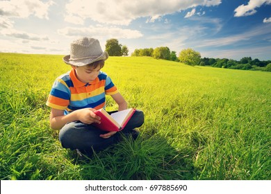 eight years old child reading a book sitting on the grass