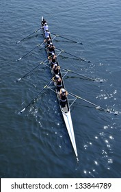 Eight young women are rowing in a skiff on a sunny day.