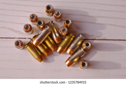Eighteen 40 caliber hollow point bullets in a group on a white wooden table shot from above