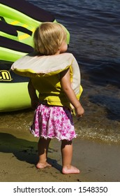 An eighteen month old toddler girl wearing a life jacket stands on the shore.