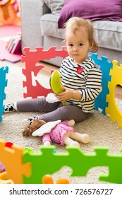 Eighteen months old toddler girl playing with her plastic toys on the mat in the living room