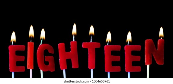 Eighteen spellt out in red birthday candles against a black background