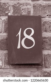 Eighteen Street Sign on Stone Wall in Black and White Sepia Tone