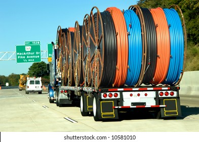 Eighteen wheeler hauls big load of plastic hose.  Each reel contains black, orange and blue hose.  Interstate signs in background.