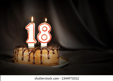 Eighteen years anniversary. Birthday chocolate cake with white burning candles in the form of number Eighteen. Dark background with black cloth