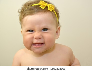 Eight-month-old girl, portrait close-up against a bright background