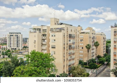 Eight-story residential buildings of 70-s 20 century sunk in green trees. The new modern living tower is seen in the background. Taken in Givat Nof neighborhood in Ness Ziona, Israel