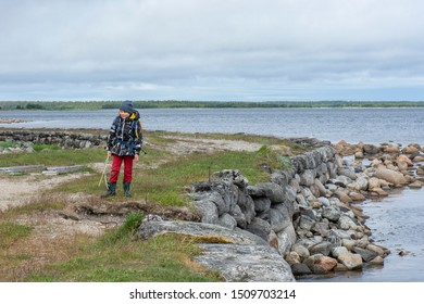 an eight-year-old boy with a backpack and in warm clothes stands on a dam across the strait in the White Sea