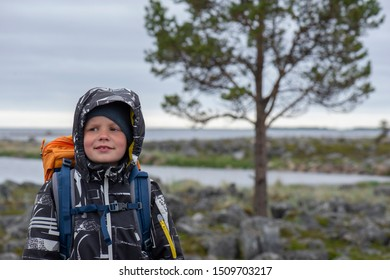 eight-year-old boy with a backpack and in a warm jacket on the background of the summer North Sea