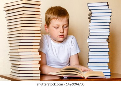 eight-year-old Caucasian boy in a white t-shirt reading a book , sitting at the table, first grader