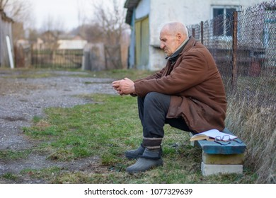an eighty-year-old elderly village man or grandfather sitting on a bench and reading a book in the background of a sunset near his home