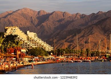 Eilat, Israel - CIRCA November 2017: Beautiful day at Israeli beach; Eilat; view of Jordanian mountains; Red Sea shore; Eilat condos; sailboats