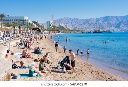 EILAT, ISRAEL - DEC. 29, 2016: People spending their Christmas and New Year vacation bathing and SUP boating in the Red Sea beach of sunny Eilat, Israel