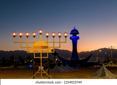 Eilat, Israel - December 11, 2018: Entrance to the city. Menorah with plate of Chabad organization. English translation of Hebrew letters on plate means Orthodox Jewish Hasidic movement
