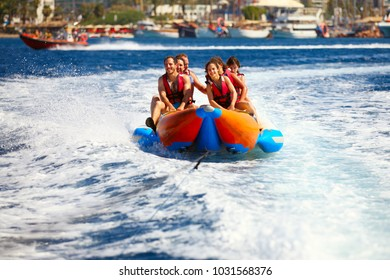 Eilat, Israel - JUNE, 24, 2017: Sea attraction, Group of young enjoying a ride on a banana boat on sunny summer day. Beach water sport