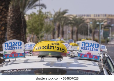 EILAT, ISRAEL - MAY 10, 2015: Detail of the luminous signs of some taxis, at the airport airport station, with palm tree walk in blurred background