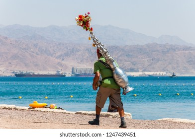 Eilat, Israel - May 15, 2012: Man with red hat caring authentic tea vessel container on his back, offering hot drink to the tourists on Eilat beach, Israel