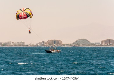 Eilat, Israel - May 15, 2012: Parasailing is a recreational kiting activity where a person is towed behind a boat while attached to a canopy wing that reminds a parachute, known as a parasail wing.