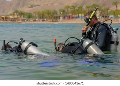 Eilat, Israel - May 2018: Scuba diving course. Men with breathing apparatus are diving into sea. Sport activity vacation. A popular water sport and leisure activity