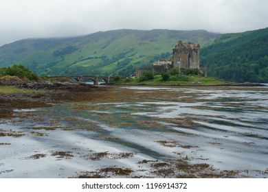 Eilean Donan castle with bridge on loch duich  mist in the background, small waves in foreground