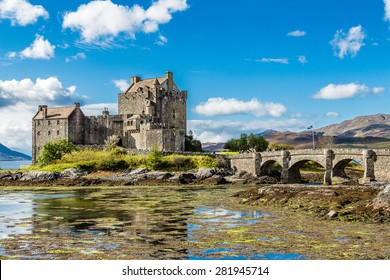 EILEAN DONAN CASTLE, DORNIE, SCOTLAND - SEPTEMBER 20, 2014: colourful view during low tide in a sunny and bright day as wind waves the Scottish flag. Tourists pay visit when touring Highland and Skye.