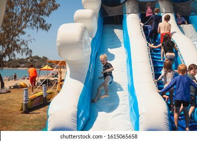 Eimeo, Queensland / Australia - September 15 2019: Children having a terrific time on inflatable water slides at event organised by the Eimeo Surf Lifesaving club at Eimeo Beach