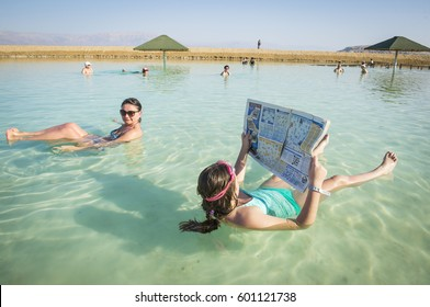 EIN BOCKEK (DEAD SEA), ISRAEL - MARCH 08, 2017: Young woman reads a newspaper floating in the waters of the Dead Sea in Israel