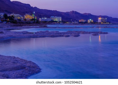 EIN BOKEK, ISRAEL - MARCH 16, 2018: Sunset view of salt formations in the Dead Sea, Ein Bokek resort, and visitors. Southern Israel