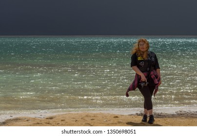 Ein Bokek, Israel - March 2019: woman-photograper at the Dead sea beach