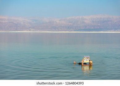 Ein Bokek, Israel: September 16th, 2018: A woman floating in the water of the dead sea while reading a newspaper.