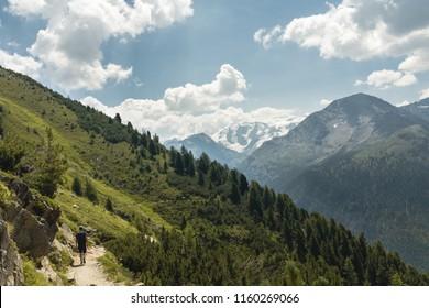 Ein einsamer Wanderer marschiert durch eine alpine Berglandschaft. Der Weg führt durch grüne Bäume und Sträucher. Aufgenommen bei Tageslicht.