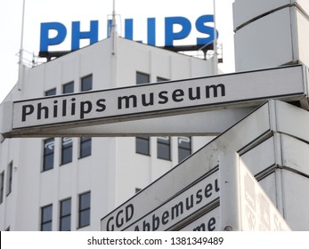 Eindhoven, The Netherlands - 23 April 2019: Signpost direction Philips museum. Background building Witte Dame with blue Philips logo. Famous landmark. Part of as serie.