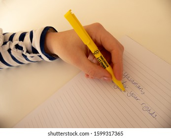 Eindhoven, The Netherlands - 27 December 2019:  young woman writes a letter with a yellow amnesty international pencil. Write for your rights, part of a serie.