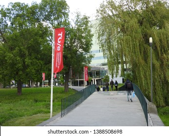 Eindhoven, The Netherlands - 4 Mai 2019: Technical University Eindhoven. Students walk over the bridge, way to the entrance. Red flags with university of technology in park.Brainport. Part of a serie.