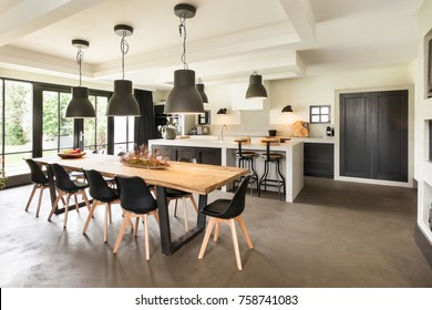 Eindhoven, The Netherlands - December 19, 2015: Large and modern open kitchen interior with island, dining table and contemporary concrete floor
