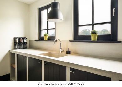 Eindhoven, The Netherlands - December 19, 2015: Kitchen interior with windows, sink, natural style counter top and cabinets