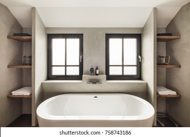 Eindhoven, The Netherlands - December 19, 2015: Interior of a modern batroom with bathtub, windows and shelves in natural colors.