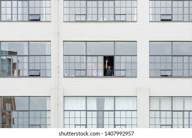 Eindhoven, the Netherlands, June 11th 2018. Front view of the facade of the old Philips building with a happy man waving from his loft on Strijp S Eindhoven