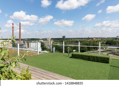 Eindhoven, The Netherlands, June 6th 2019. View from the rooftop garden with lots of greenery at Strijp S to the old chimeneys at the Strijp T building with a blue sky on a sunny day
