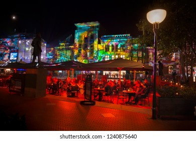 "Eindhoven, The Netherlands - November 14, 2018: Square Markt with terrace and colorful light projection, artwork ""Immersive decelerator"" (Georg Reisch of Pani) during light art festival GLOW Eindhoven"