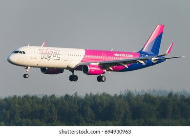 EINDHOVEN, THE NETHERLANDS - SEPTEMBER 2, 2016: A Wizz Air commercial passenger airplane is ready to land at the Eindhoven airport. Wizz Air is a Hungarian low cost airline.