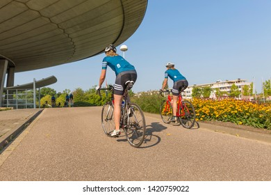 Eindhoven, The Netherlands, September 3rd 2017, Two women race cycling through Eindhoven with the Evoluon and flowers in the background on a sunny day